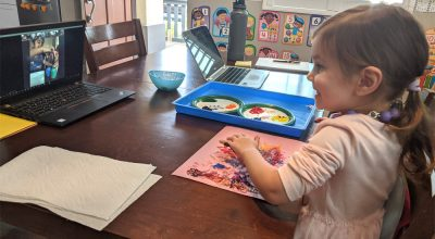 A smiling girl works on an art project that the teacher is demonstrating in a video.